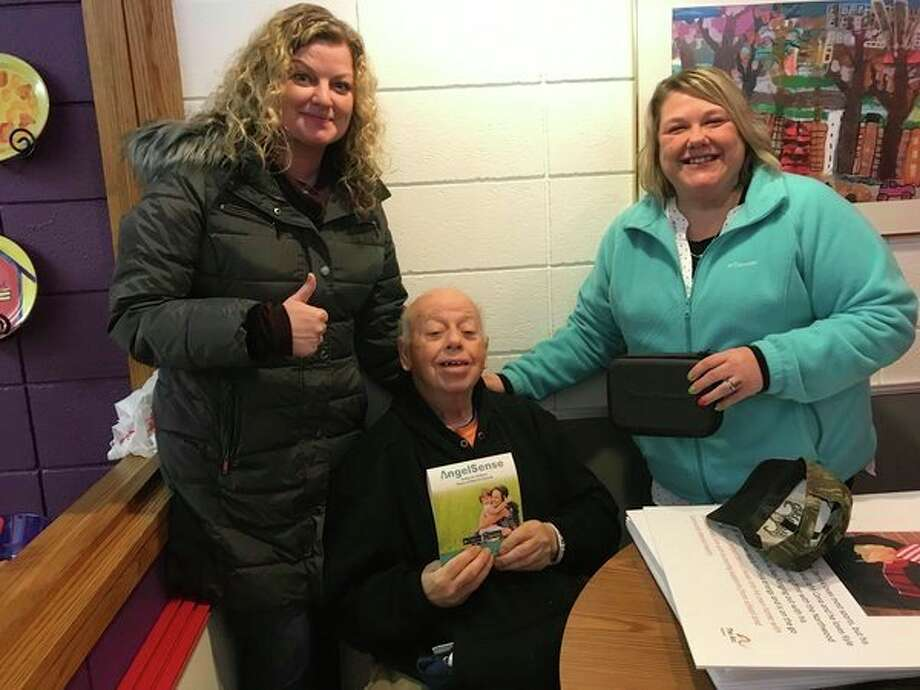 Melvin Fisher, center, the first person to use The Arc of Midland's Project Lifesaver system 10 years ago, poses with The Arc employee Kelly Lambert and Carole Weed, a direct support professional. The Arc will begin using the Angel Sense GPS system. (Photo provided)