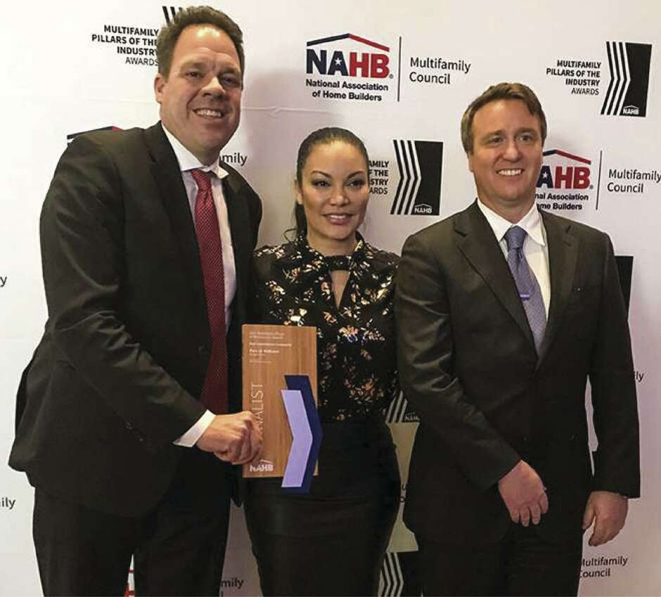 Ben Lemieux, chairman of Surge Homes, left, and Louis Conrad, president of Surge Homes, right, are congratulated by NAHB Awards emcee Egypt Sherrod.