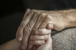 A stock photo of a young woman holding her Elderly fathers hands who is currently being cared for on a home hospice program. Photographed using the Canon EOS 1DX Mark II. Perfect for designs or articles about caring for the elderly or home hospice care and nursing.