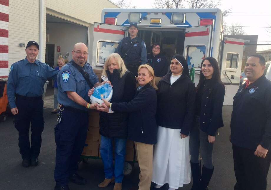 Stamford EMS, the Stamford Paramedic Association and families from Our Lady of Grace School donated 70 complete Thanksgiving dinners To Stamford Food Bank. Front row, left to right: Kirk McClennan; Peter Kessler, president of the Stamford Paramedic Association, local 684; Kate Lombardo, executive director of the Food Bank of Lower Fairfield County; Patricia Squires, Stamford EMS Chief and CEO; Sister Rosna; Francine Manfredi; Eddie Browne. Back row: James Connelly and Jessica Anderson. Photo: Contributed Photo / Contributed Photo / Stamford Advocate Contributed
