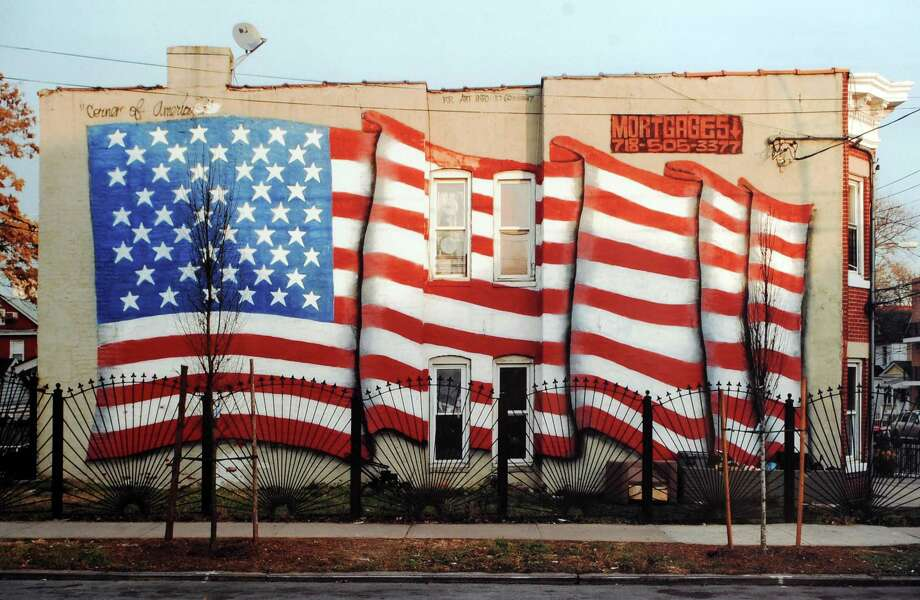 "A photographed titled ""Mural,"" taken in Queens, New York, 2008, by Darien native Robert Carley, an artist and photographer, at the Bruce Museum in Greenwich, Saturday, Sept. 7, 2013. After Carley witnessed the Twin Towers collapse from his third floor window in Stamford on 9/11, he has made it his quest to capture the American spirit by photographing the American Flag. Carley's exhibition, ""Flags Across America,"" is featured at the Bruce Museum until Sept. 22. Photo: File Photo / Greenwich Time contributed"