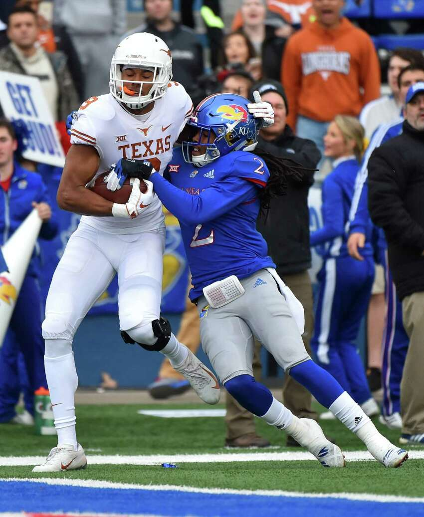 LAWRENCE, KANSAS - NOVEMBER 23: Wide receiver Collin Johnson #9 of the Texas Longhorns goes in for a touchdown against cornerback Corione Harris #2 of the Kansas Jayhawks in first quarter at Memorial Stadium on November 23, 2018 in Lawrence, Kansas.