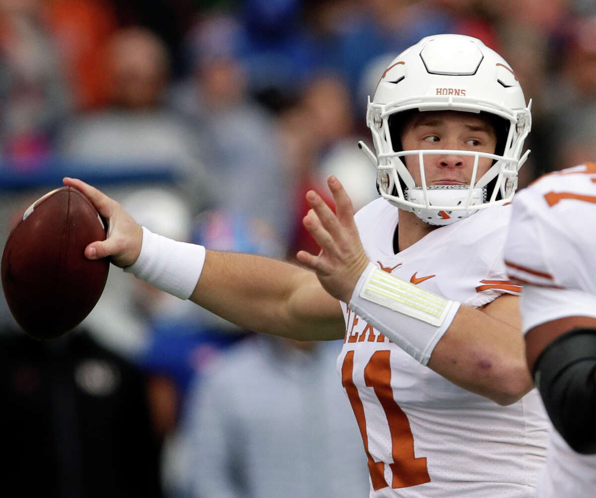 Texas quarterback Sam Ehlinger (11) passes to a teammate during the first half of an NCAA college football game against Kansas in Lawrence, Kan., Friday, Nov. 23, 2018. (AP Photo/Orlin Wagner)