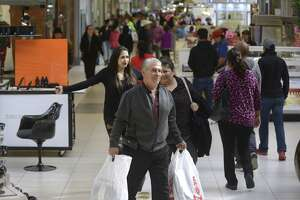 Shoppers, some with purchases, walk at South Park Mall on Black Friday, Nov. 23, 2018.