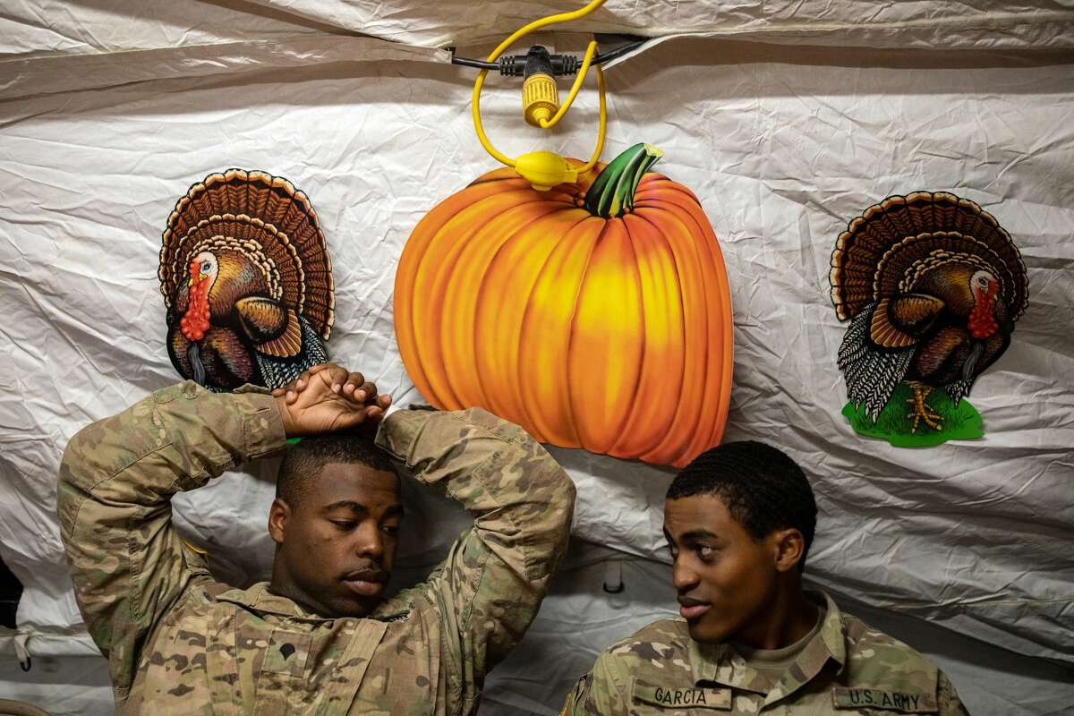 DONNA, TX - NOVEMBER 22: (Left to right) Specialists Krayveon Harris and Austin Garcia relax after eating a Thanksgiving meal as troops deployed to the U.S.-Mexico border celebrate the holiday at a base near the Donna-Rio Bravo International Bridge on November 22, 2018 in Donna, Texas. Culinary specialists prepared 34 Turkeys along with a full Thanksgiving buffet for the hundreds of troops stationed between Donna and Weslaco, Texas. (Photo by Tamir Kalifa/Getty Images)