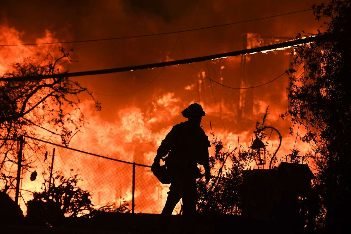 (FILES) In this file photo taken on November 9, 2018, a firefighter is silhouetted by a burning home along Pacific Coast Highway (Highway 1) during the Woolsey Fire in Malibu, California. - Climate change is already hurting the US and global economies and its effects will get worse unless more drastic action is taken to cut carbon emissions, a major US government report warned on Friday, November 23, 2018.