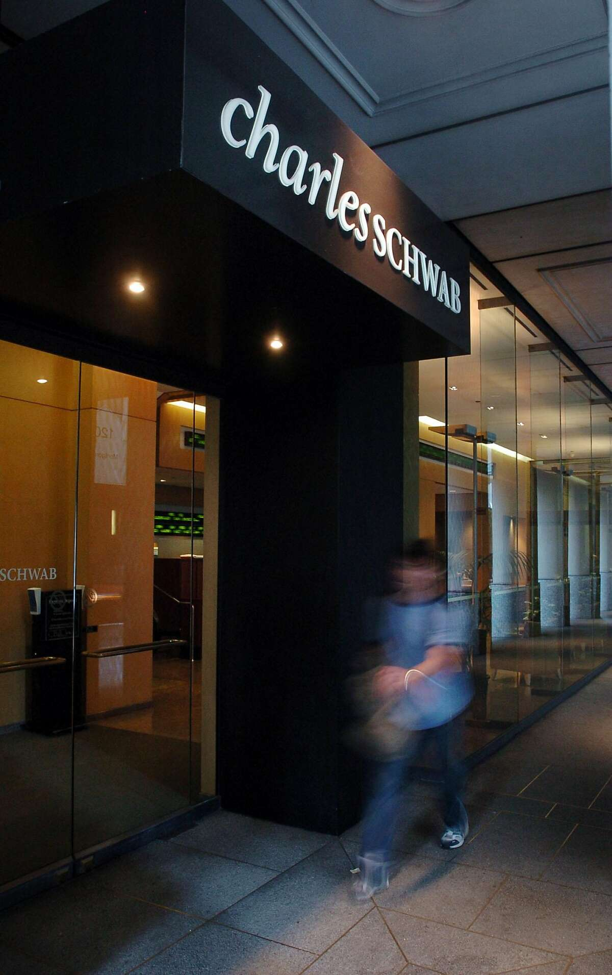 A pedestrian walks past the entrance to a Charles Schwab branch in San Francisco on Monday Oct. 17, 2005. San Francisco-based Charles Schwab Corp.'s quarterly profit surged above $200 million for the first time since the dot-com boom, continuing a comeback that has been orchestrated by the stock brokerage's founder. (AP Photo/Jakub Mosur)
