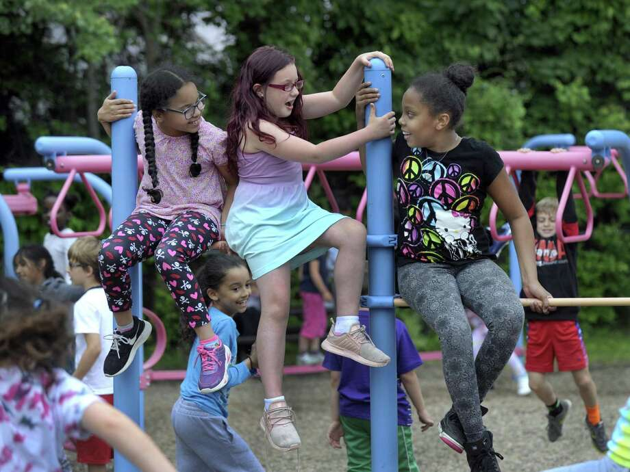 From left, Rebecca Araujl, Alexis Garcia, both 8, and Jahnaiya Reyes, 9, chat on the bars at on the playground during recess Wednesday, June 6, 2018. Parents and teachers at Pembroke Elementary are trying to raise $150,000 for a new playground and park at the school that would be more accessible to the school's 90 special needs students. Photo: Carol Kaliff / Hearst Connecticut Media / The News-Times