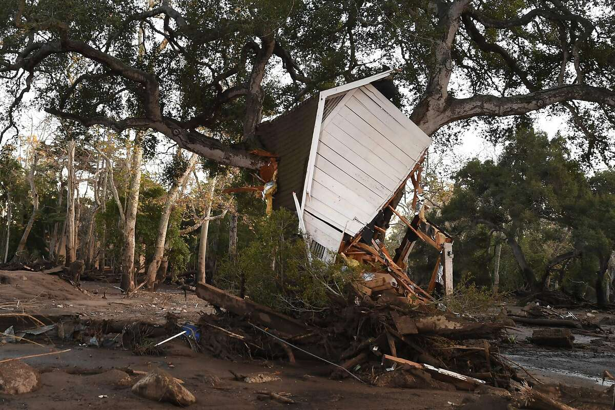 (FILES) In this file photo taken on January 10, 2018, a building uprooted by a massive mudslide is lodged in a tree in Montecito, California. - Climate change is already hurting the US and global economies and its effects will get worse unless more drastic action is taken to cut carbon emissions, a major US government report warned on Friday, November 23, 2018.