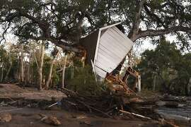 """(FILES) In this file photo taken on January 10, 2018, a building uprooted by a massive mudslide is lodged in a tree in Montecito, California. - Climate change is already hurting the US and global economies and its effects will get worse unless more drastic action is taken to cut carbon emissions, a major US government report warned on Friday, November 23, 2018.  """"Without substantial and sustained global mitigation and regional adaptation efforts, climate change is expected to cause growing losses to American infrastructure and property and impede the rate of economic growth over this century,"""" said the latest edition of the National Climate Assessment. (Photo by Robyn Beck / AFP)ROBYN BECK/AFP/Getty Images"""