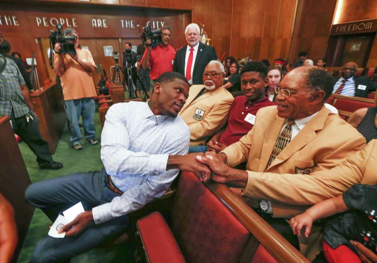 Andre Johnson, former Texans wide receiver, shakes hands with NFL Hall of Famers and chats with Elvin Bethea before he was honored with
