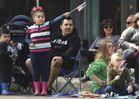 """Girls wave flags to show their supports during the 100th annual Porterville Veterans Day Parade downtown Porterville, Calif., Monday, Nov. 12, 2018. Spectators enjoy 125 entries, displaying their """"Armistice Day"""" theme. (Chieko Hara/The Porterville Recorder via AP)"""