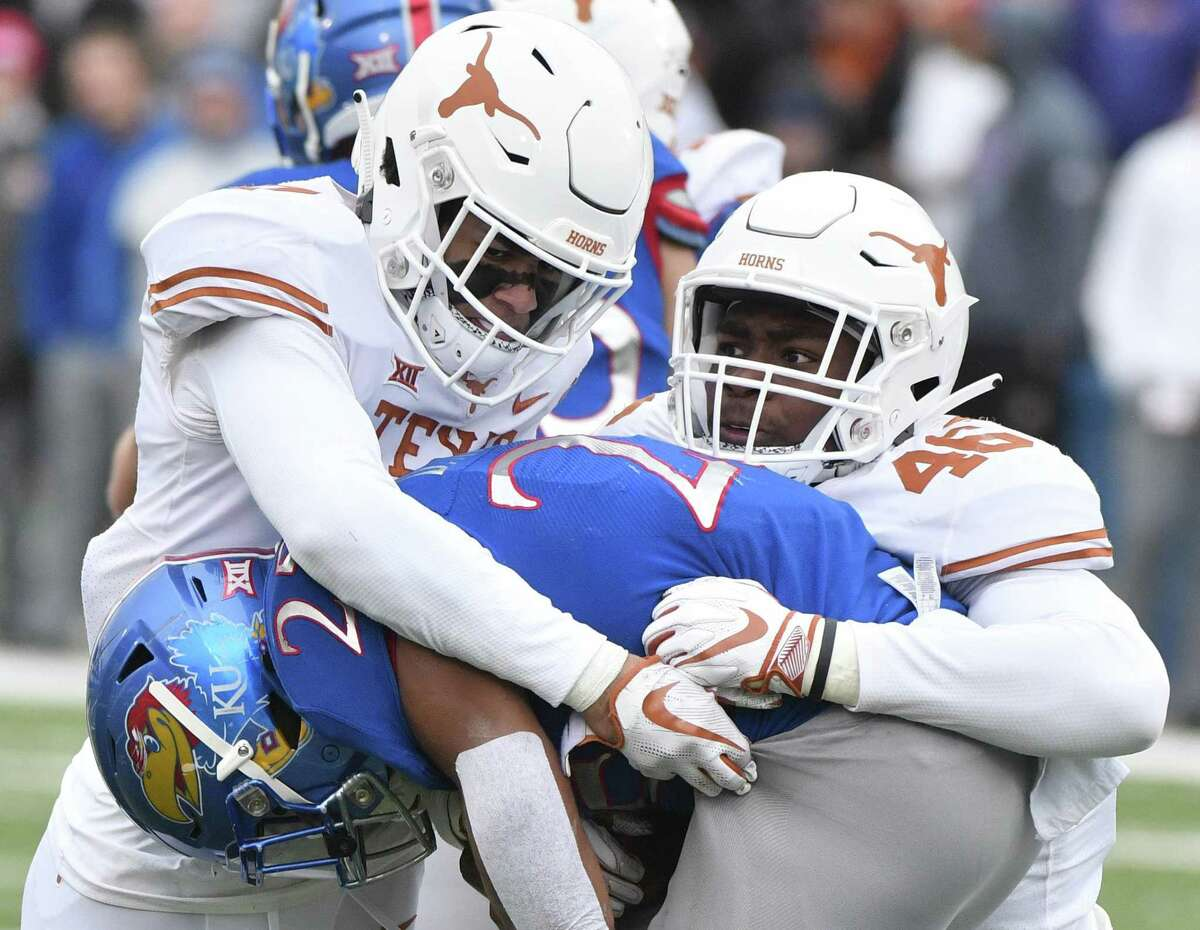 Running back Dom Williams (25) of the Kansas Jayhawks is tackled by defensive back Caden Sterns #(7) and Joseph Ossai (46) of the Texas Longhorns in second quarter at Memorial Stadium on November 23, 2018 in Lawrence, Kansas.
