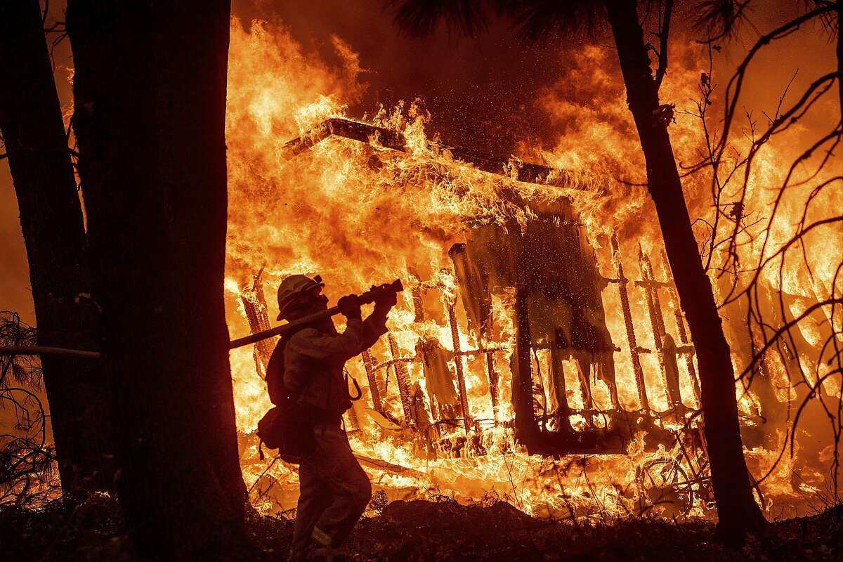 FILE - In this Nov. 9, 2018 file photo, firefighter Jose Corona sprays water as flames from the Camp Fire consume a home in Magalia, Calif. Experts warn this year's dry spring may lead to another severe fire season . (AP Photo/Noah Berger, File)