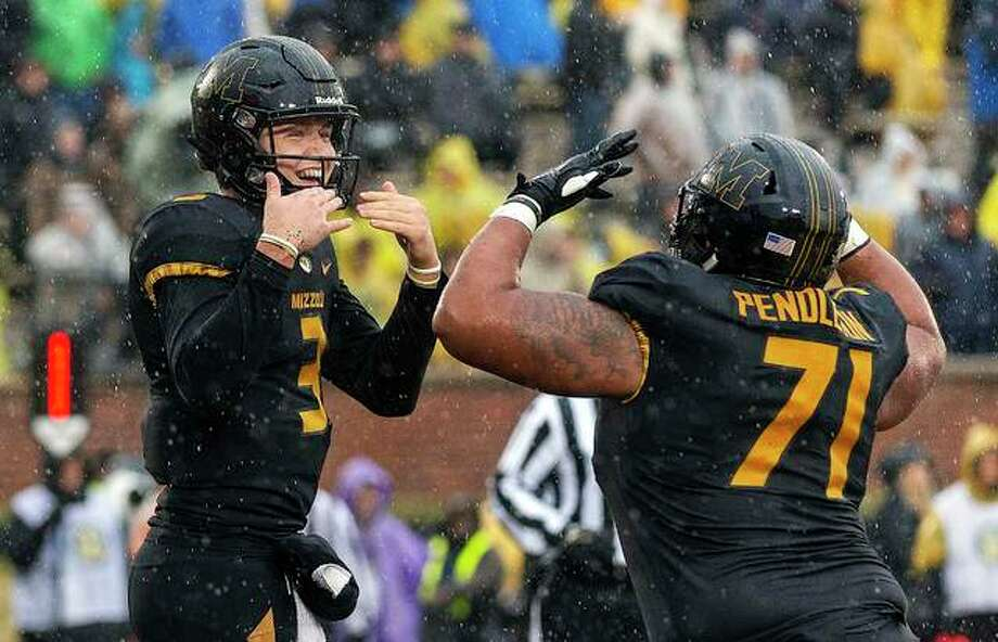 Missouri quarterback Drew Lock, left, celebrates with teammate Kevin Pendleton after Lock scored a touchdown Friday against Arkansas in Columbia, Mo. Photo: AP Photo
