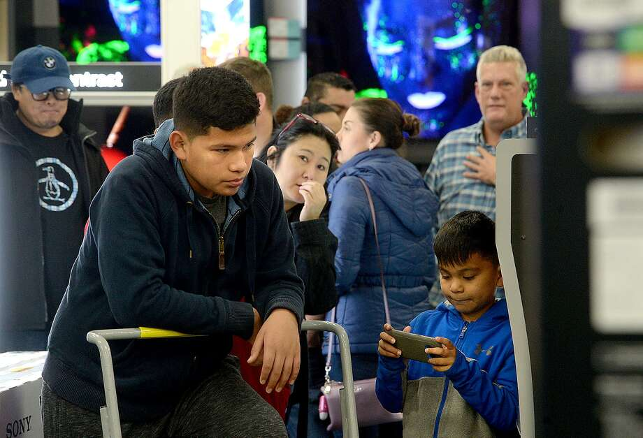 """Xavier Galvan, 13, rests on is cart while brother Jyovanny, 7, plays a game as the family wait to purchase their 55"""" television, the special doorbuster deal on Black Friday. The Galvan family was first in line to await the door opening and ensure they got a ticket for the featured item. They camped out at the store, having arrived Thursday night at 11 p.m.  Photo taken Friday, November 23, 2018  Kim Brent/The Enterprise Photo: Kim Brent / The Enterprise / BEN"""