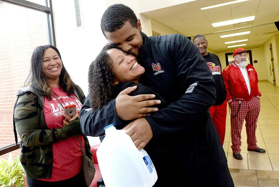 Reggie Boseman hugs his sister Summer, who joimed family in the gathering for a send-off Friday at the Dauphin Athletic Complex. Fans and family formed a tunnel, clapping as Lamar players and coaches made their way to board their buses and set out for Northern Iowa, where they will play in their first FCS play-off game Saturday.