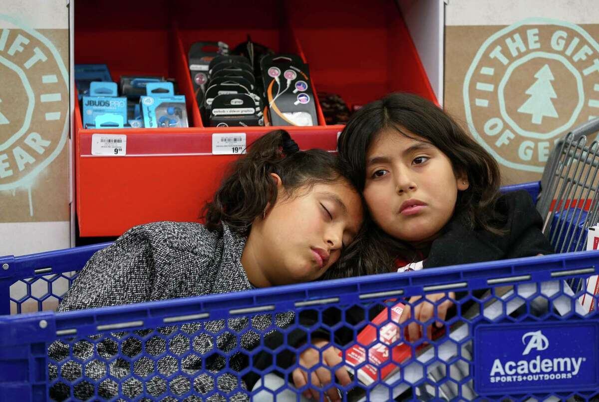 """Ten-year-old Ashley Castillo, left, sleeps on her sister's, Daisy, shoulder as their family shopped at the Academy Sports + Outdoors store during Black Friday Friday, Nov. 23, 2018, in Speing, Texas. The two girls were excited to go shopping after winning six dollars in a game of """"La Loteria"""" after Thanksgiving dinner at their grandmother's home. """"So far they haven't spend any of it,"""" said their mother, Rosa Castillo."""
