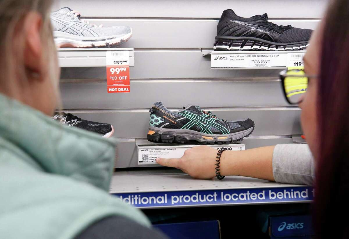 Deborah Weckerly, 35, left, and Krystal Lind, 35, shop for shoes at the Academy Sports + Outdoors store during Black Friday Friday, Nov. 23, 2018, in Spring, Texas.