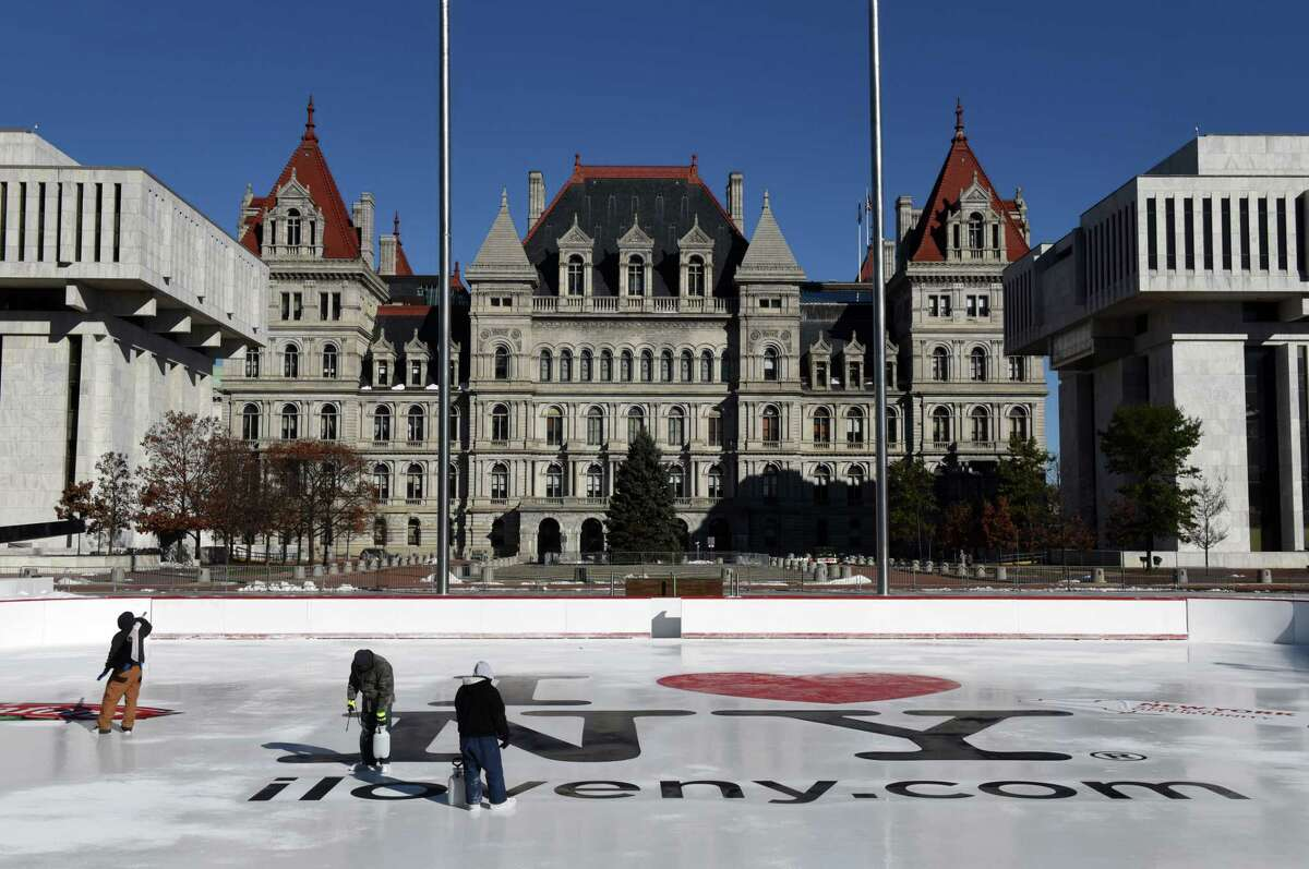Logos are applied to the Empire State Plaza ice rink by a work crew from the Office of General services on Friday, Nov. 23, 2018, in Albany, N.Y. The skating facility is scheduled to open on Friday, November 30, weather permitting. Admission is free, there is also a free skate rental offered each Saturday courtesy of Hannaford Supermarkets. (Will Waldron/Times Union)