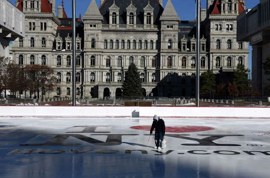 Logos are applied to the Empire State Plaza ice rink by a work crew from the Office of General services on Friday, Nov. 23, 2018, in Albany, N.Y. The skating facility is scheduled to open on Friday, November 30, weather permitting.  Admission is free, there is also a free skate rental offered each Saturday courtesy of Hannaford Supermarkets. (Will Waldron/Times Union) Photo: Will Waldron