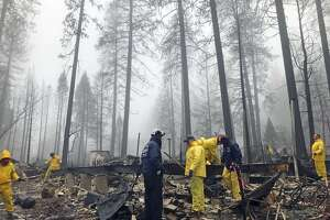 After a brief delay to let a downpour pass, volunteers resume their search for human remains at a mobile home park in Paradise, Calif., Friday, Nov. 23, 2018. A team from Orange County in Southern California is among several teams conducting a second search of a mobile home park after the deadly Camp wildfire torched part of Butte County in Northern California. Task force leader Craig Covey, in blue jacket at center, says his team is doing a second search because there are outstanding reports of missing people whose last known address was at the mobile home park. (AP Photo/Kathleen Ronayne)