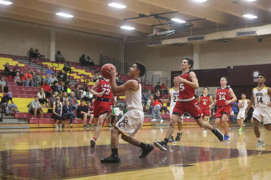 Deer Park's Michael Romero drives in against Clear Lake's defense  for two of his nine points in the quarterfinal contest Friday afternoon. The score gave Deer Park a 30-25 lead. Photo: Robert Avery