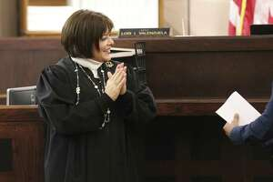 Judge Lori I. Valenzuela applauds a military veteran's completion of a treatment program on Nov. 15. Valenzuela's court is one of two courts in Bexar County that handles felony cases  committed by  veterans.