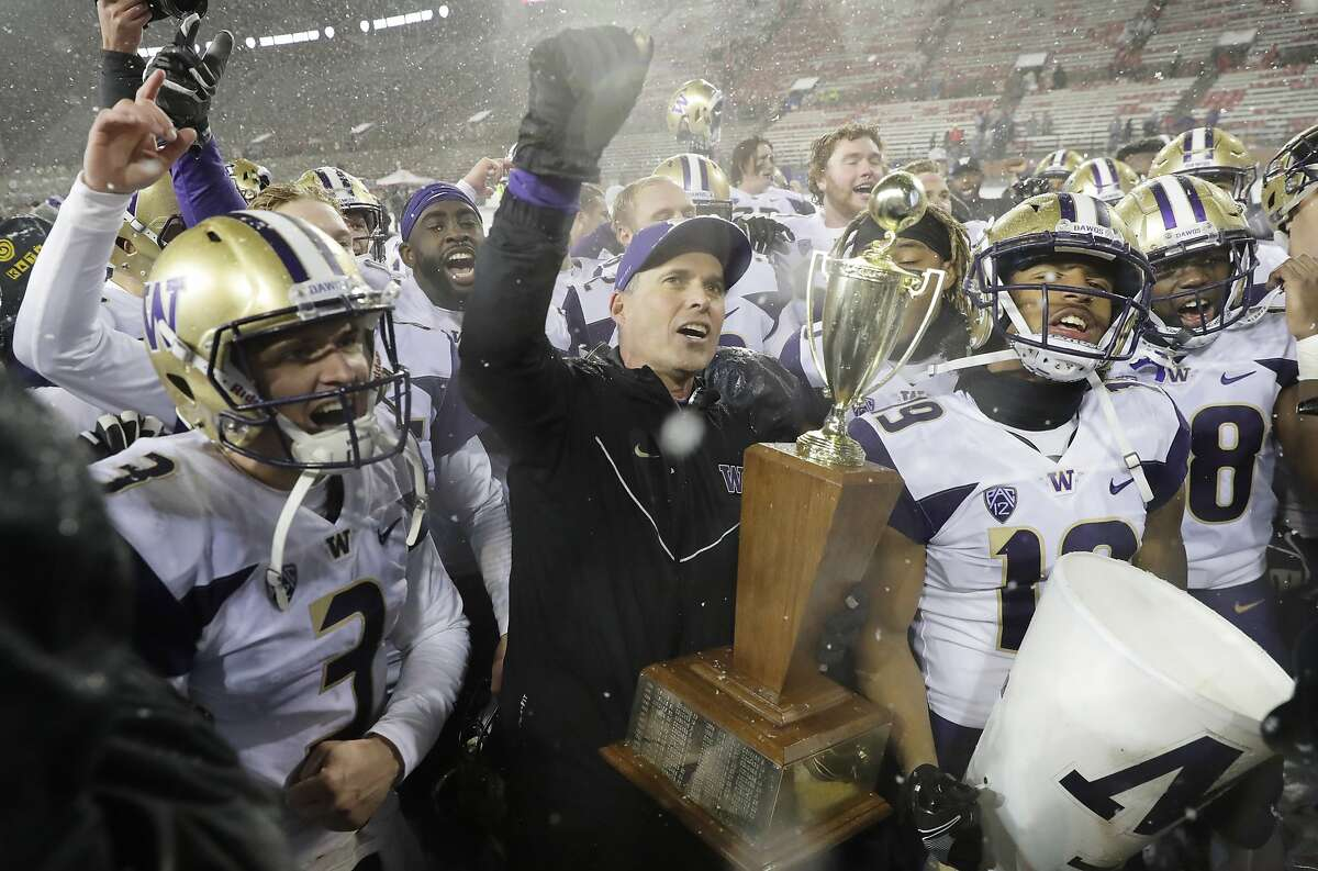 Washington coach Chris Petersen, center, holds the Apple Cup trophy as he celebrates with quarterback Jake Browning, left, and the rest of the team after Washington defeated Washington State 28-15 in an NCAA college football game Friday, Nov. 23, 2018, in Pullman, Wash. (AP Photo/Ted S. Warren)