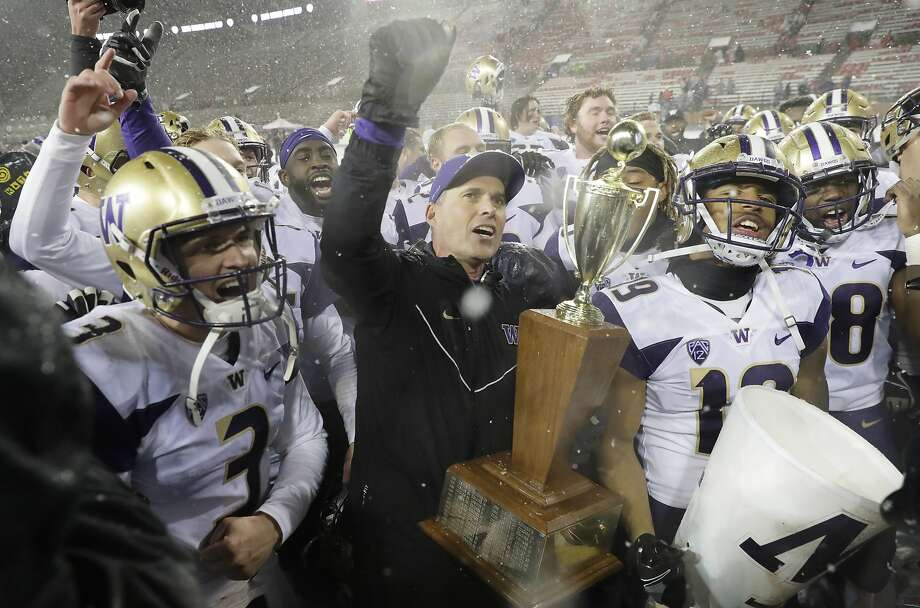Washington coach Chris Petersen, center, holds the Apple Cup trophy as he celebrates with quarterback Jake Browning, left, and the rest of the team after Washington defeated Washington State 28-15 in an NCAA college football game Friday, Nov. 23, 2018, in Pullman, Wash. (AP Photo/Ted S. Warren) Photo: Ted S. Warren / Associated Press