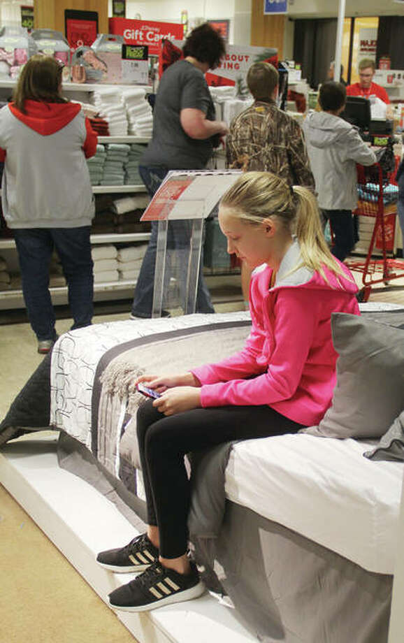 Ava Clowers, 11, of Hardin, sits on a bed at JC Penney at Alton Square while her family checks out early Friday afternoon. Shoppers came out for Black Friday sales in what has been the traditional start of the Christmas shopping season. According to the National Retail Federation, shoppers will spend an average of $1,007.24 per person on holiday shopping, up about 4 percent from last year. Photo: Scott Cousins | The Telegraph