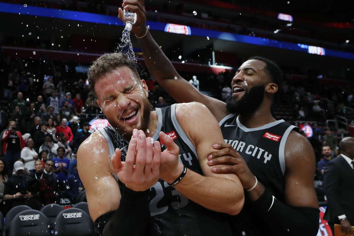 Detroit Pistons center Andre Drummond, right, pours water onto forward Blake Griffin after the Pistons defeated the Houston Rockets 116-111 in overtime in an NBA basketball game Friday, Nov. 23, 2018, in Detroit. (AP Photo/Carlos Osorio)