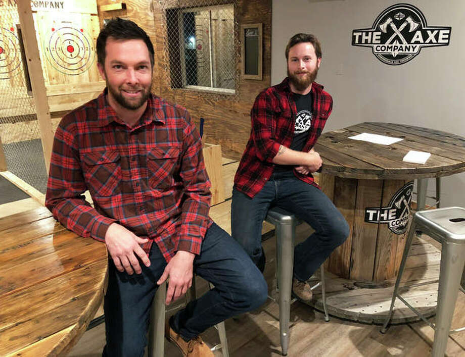 Co-owners Tim Jenkins, left, and Brendan Hampton, pose in their recently launched business The Axe Company during a soft opening event Wednesday night. The locally-owned axe throwing facility is located at 20 Kettle Drive in Glen Carbon and is offering specials to visitors today in honor of Small Business Saturday. Co-owner Adam Merkel is not pictured. Photo: Brittany Johnson | The Intelligencer