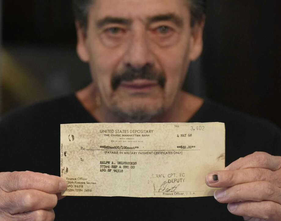 "Vietnam veteran Ralph Del Vecchio holds an uncashed $82 check for his wartime grave registration duty inside his home in Stamford, Conn. Wednesday, Nov. 21, 2018. With only days left in his tour, Del Vecchio was assigned to bag the bodies of his fallen comrades, load them on a truck and then a cargo plane to a larger airport where they were transported home. For the ""extra duty"" the Army gave him a check for $82, which he says he will never cash. Photo: Tyler Sizemore / Hearst Connecticut Media / Greenwich Time"