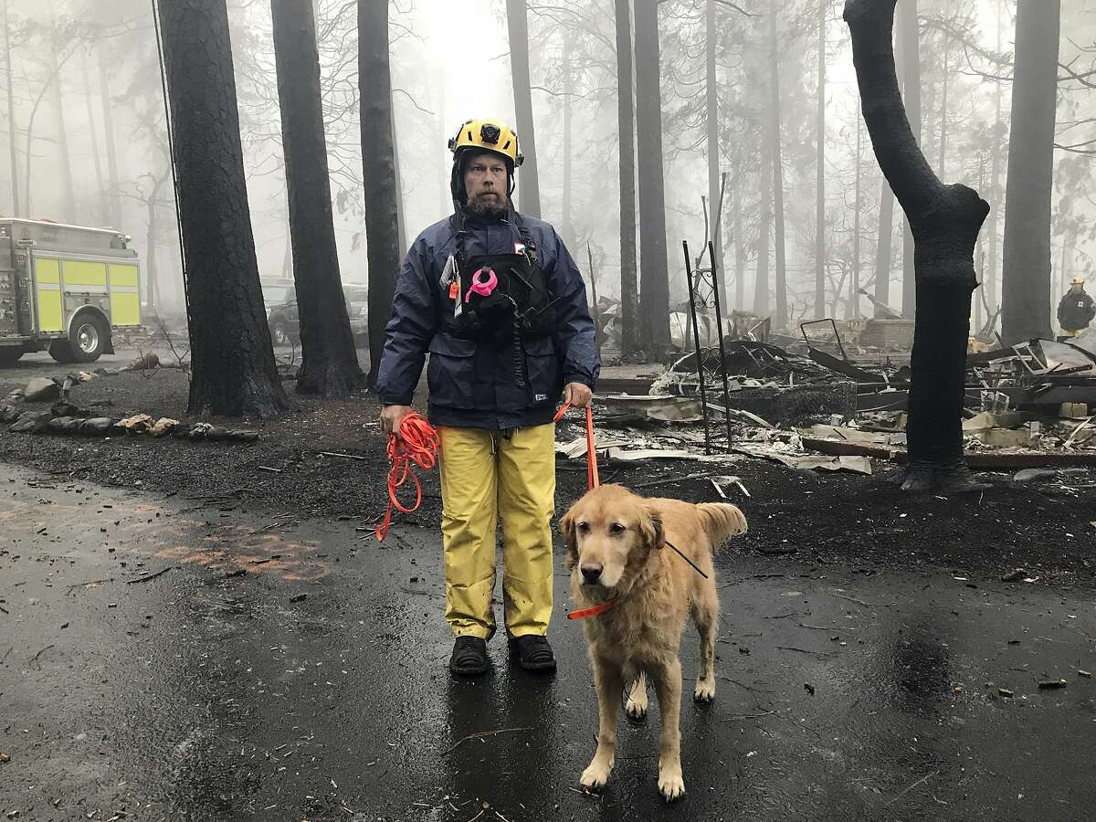 Eric Darling and his dog Wyatt are part of a search team from Orange County in Southern California who are among several teams conducting a second search of a mobile home park after the deadly Camp Fire in Paradise, Calif., Friday, Nov. 23, 2018. The team is doing a second search because there are outstanding reports of missing people whose last known address was at the mobile home park. They look for clues that may indicate someone couldn't get out, such as a car in the driveway or a wheelchair ramp. (AP Photo/Kathleen Ronayne)
