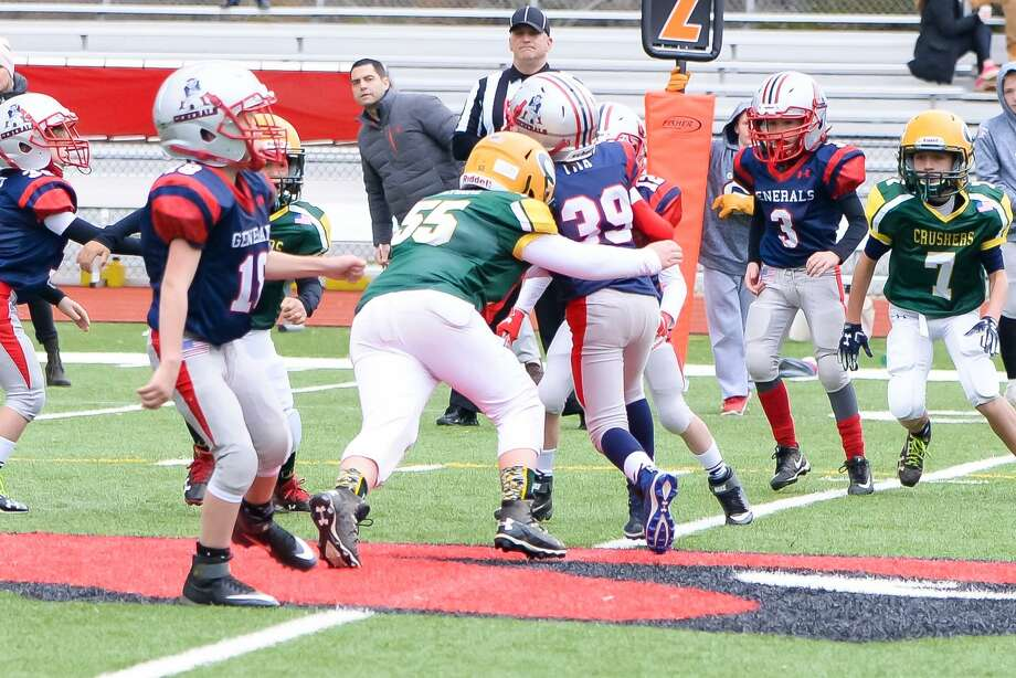 Bantam Crusher Mickey Petrone (55) makes at tackle against the Generals. Photo: Contributed Photo / Contributed Photo / Stamford Advocate Contributed