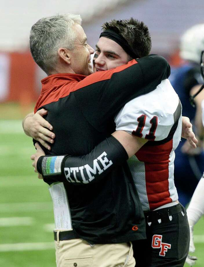 Glens Falls' Joseph Girard III, right, hugs head coach Patrick Lilac after their win in the 2018 Class B NYSPHSAA Football Championships in Syracuse, N.Y., Saturday, Nov. 24, 2018. Glens Falls claimed the Class B title with a 55-32 win over Batavia-V. (Adrian Kraus / Special to the Times Union) Photo: Adrian Kraus / © akoPhoto 2018