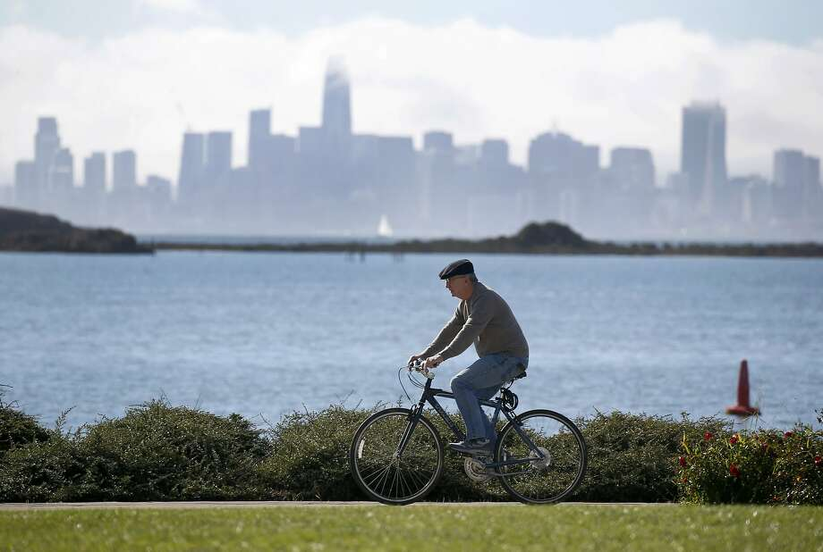 A Bicyclist Pedals Past The San Francisco Skyline At Lucretia W Edwards Shoreline Park In