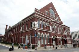 """FILE - In this June 8, 2015, file photo, pedestrians pass by the Ryman Auditorium in Nashville, Tenn. Granville Automatic, which began in Atlanta and is now based in Nashville, recently released its album """"Radio Hymns."""" The title track recounts how the Ryman Auditorium was saved just as it was about to be demolished in the 1970s. (AP Photo/Mark Humphrey, File)"""