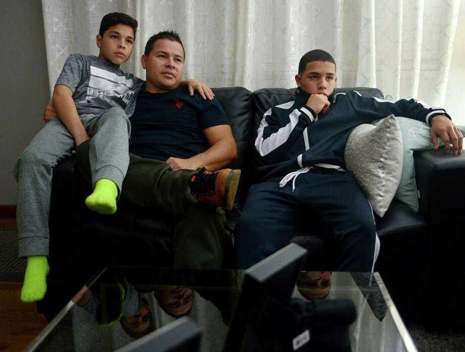Jose Vasquez, with his sons, Alan, 11, and Jose, 14, on Wednesday at their home in Norwalk. Vasquez, who is Venezulean but has lived in Norwalk for 17 years, was with his son at a little league baseball tournament in Texas over the summer when the car he was driving was randomly stopped by border patrol. Vasquez originally came into the country legally, but has since overstayed his visa. Since he had no criminal history, Vasquez and his son, Alan, were detained and eventually were released back to Connecticut. Vasquez is fighting his deportation order in the hopes that he will remain in America with his wife and children, rather than return to Venezuela.  p.p1 {margin: 0.0px 0.0px 0.0px 0.0px; font: 9.0px Arial} span.s1 {font-kerning: none}  (An earlier version of this story reported that Norwalk father Jose Vasquez was detained at a detention center near the Mexican border with his son, Jose. But Vasquez was detained with his son, Alan.) Photo: Erik Trautmann / Hearst Connecticut Media / Norwalk Hour