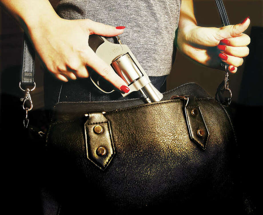 A young woman pulls a Smith & Wesson .38 Special snub nose handgun from her purse. While not always the most efficient place for conceal carry, many women use purses and special purses with holsters built into the lining for conceal carry. Illinois conceal carry permit requests are backed up due, at least in part, to high volume, and with renewals beginning next spring, bigger problems could be on the horizon. Photo: John Badman | The Telegraph
