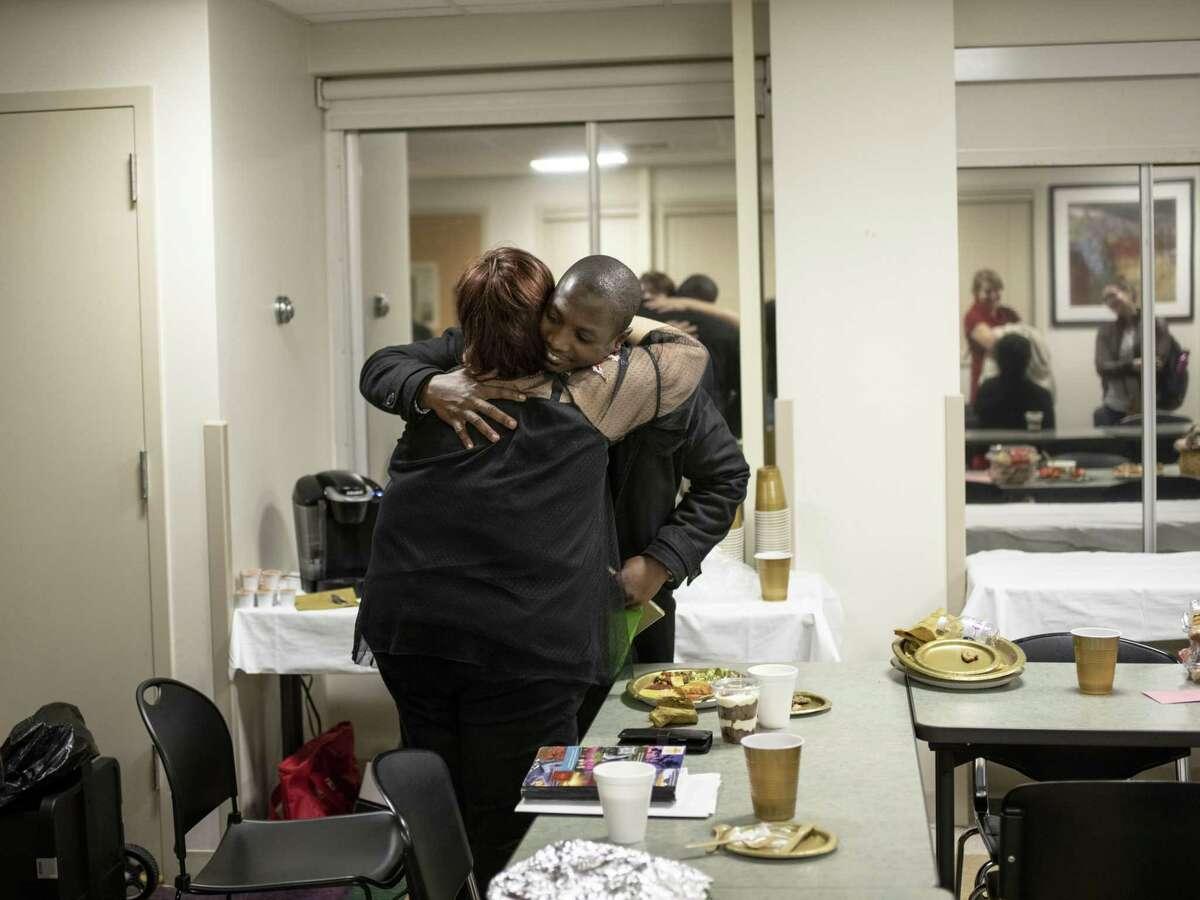 Lindy Ochoa, left, a registered nurse who coordinates the volunteer cuddlers program at Baptist Medical Center, hugs one of the volunteers, Agbeko Segbefia, during a bi-monthly appreciation dinner for them on Nov. 15, 2018.
