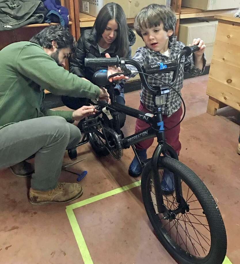 Guilford residents Tom and Maggie Ferrell, with the assistance of their 4-year-old son Bruen, assemble a bike during the 2017 Wishing Wheels Holiday Bike Drive. Photo: Sarah Page Kyrcz / For Hearst Connecticut Media / New Haven Register freelance