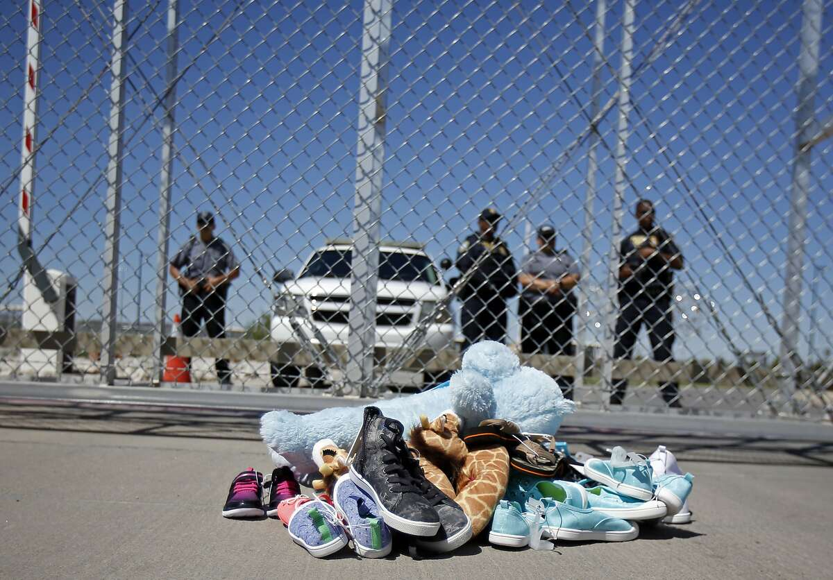 FILE- In this June 21, 2018, photo shoes and a teddy bear, brought by a group of U.S. mayors, are piled up outside a holding facility for immigrant children in Tornillo, Texas, near the Mexican border. Records obtained by The Associated Press highlight some of the problems that plague government facilities for immigrant youth. (AP Photo/Andres Leighton, File)