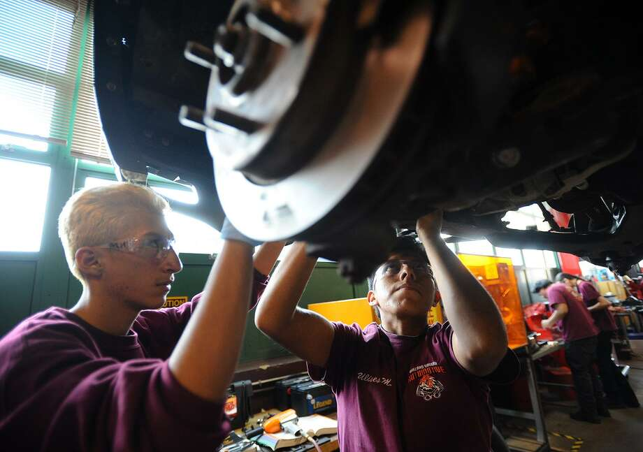 Juniors Marco Hercules, left, and Ulises Martinez, both of Bridgeport, work in the automotive shop at Bullard-Havens Technical High School in Bridgeport, Conn. on Wednesday, November 14, 2018. Photo: Brian A. Pounds / Hearst Connecticut Media / Connecticut Post