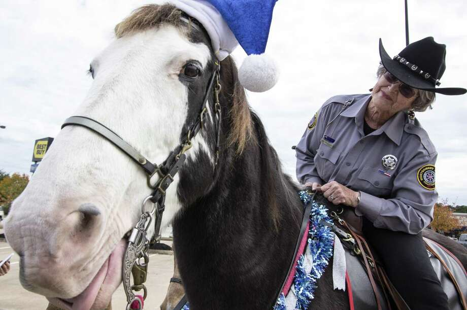 Mounted posse officer Maralyn Kinney leans over and smiles after giving mounted police horse Sonny Claus a peppermint candy treat Saturday, Nov. 24 in the Target parking lot in Conroe. Photo: Cody Bahn, Houston Chronicle / Staff Photographer / © 2018 Houston Chronicle