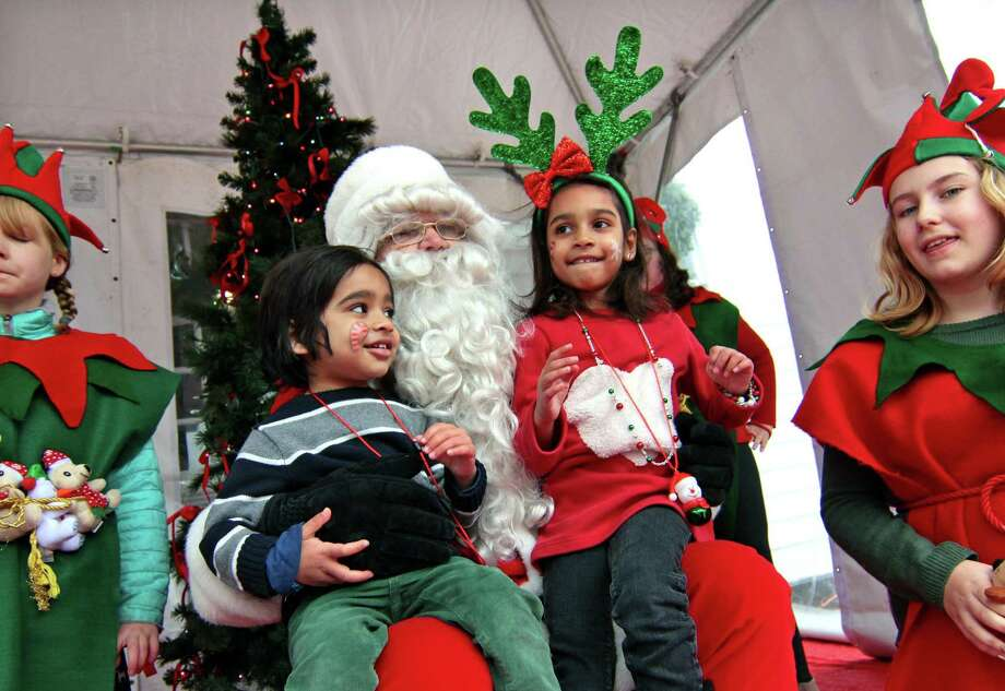 Dhruv Iyer, 3, of Southport, and his sister Moksha 5, visit with Santa on the green at Old Town Hall in Fairfield, Conn., on Saturday Nov. 24, 2018. Santa arrived at 10 a.m. via a firetruck from the Fairfield Fire Department. Along with a petting zoo and horse drawn carriage rides, local businesses and non-profit organizations showcased their products and services in tents and kiosks around the green. Photo: Christian Abraham / Hearst Connecticut Media / Connecticut Post