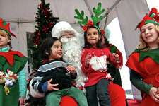 Dhruv Iyer, 3, of Southport, and his sister Moksha 5, visit with Santa on the green at Old Town Hall in Fairfield, Conn., on Saturday Nov. 24, 2018. Santa arrived at 10 a.m. via a firetruck from the Fairfield Fire Department. Along with a petting zoo and horse drawn carriage rides, local businesses and non-profit organizations showcased their products and services in tents and kiosks around the green.