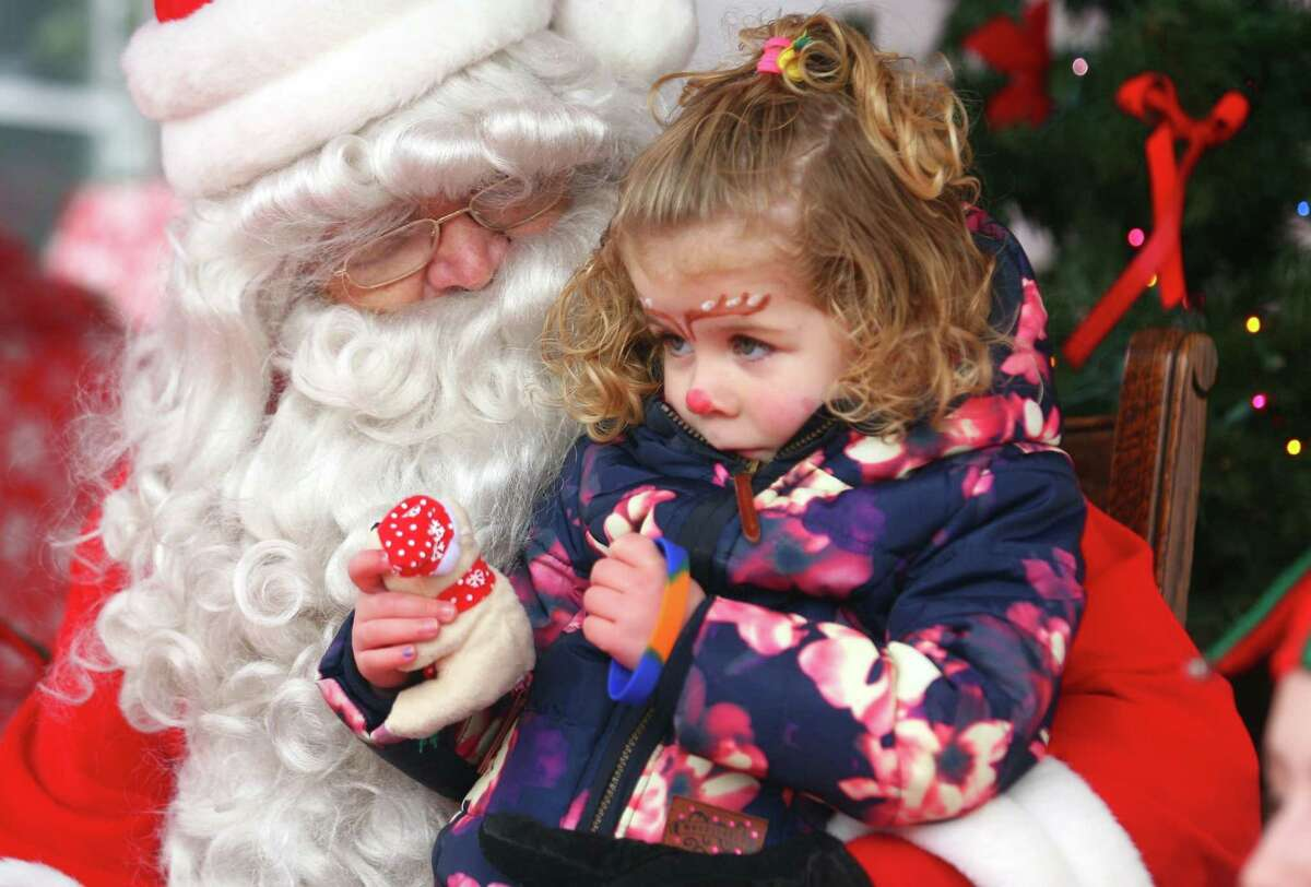 Floor Ruijter, 3, visiting family in Fairfield from the Netherlands, sits with Santa during Fairfield Chamber of Commerce's annual Santa's Arrival on the historic Town Green at Old Town Hall in Fairfield, Conn., on Saturday Nov. 24, 2018. Santa arrived at 10 a.m. via a firetruck from the Fairfield Fire Department. Along with a petting zoo and horse drawn carriage rides, local businesses and non-profit organizations showcased their products and services in tents and kiosks around the green.