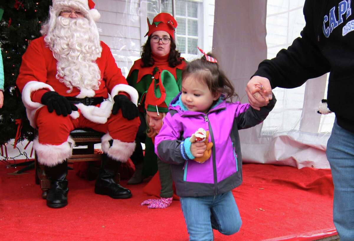 Emma O'Neill, 2, of Fairfield, visits with Santa during Fairfield Chamber of Commerce's annual Santa's Arrival on the historic Town Green at Old Town Hall in Fairfield, Conn., on Saturday Nov. 24, 2018. Santa arrived at 10 a.m. via a firetruck from the Fairfield Fire Department. Along with a petting zoo and horse drawn carriage rides, local businesses and non-profit organizations showcased their products and services in tents and kiosks around the green.